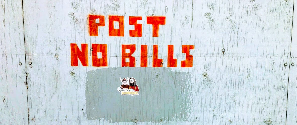 'Post no bills' stencilled on a wall with a viking and lumberjack sticker below.