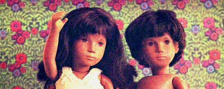 upper torsos and heads of malevolent looking dolls, against a flowery wallpaper background.